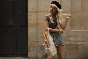 Sarah Loven standing with baguette and market bag.