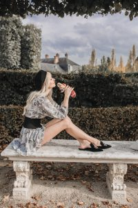 Sarah Loven sitting in the gardens at Versailles in Paris France.